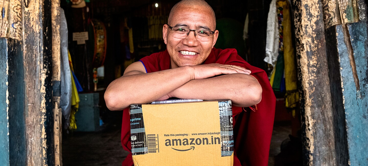A Buddhist monk in maroon-colored robes sits on a doorstep. He looks into the camera and leans his crossed arms on top of an Amazon package that sits in his lap.