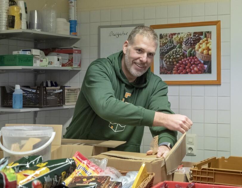 Ein Mitarbeiter im grünen Hoodie sortiert Waren