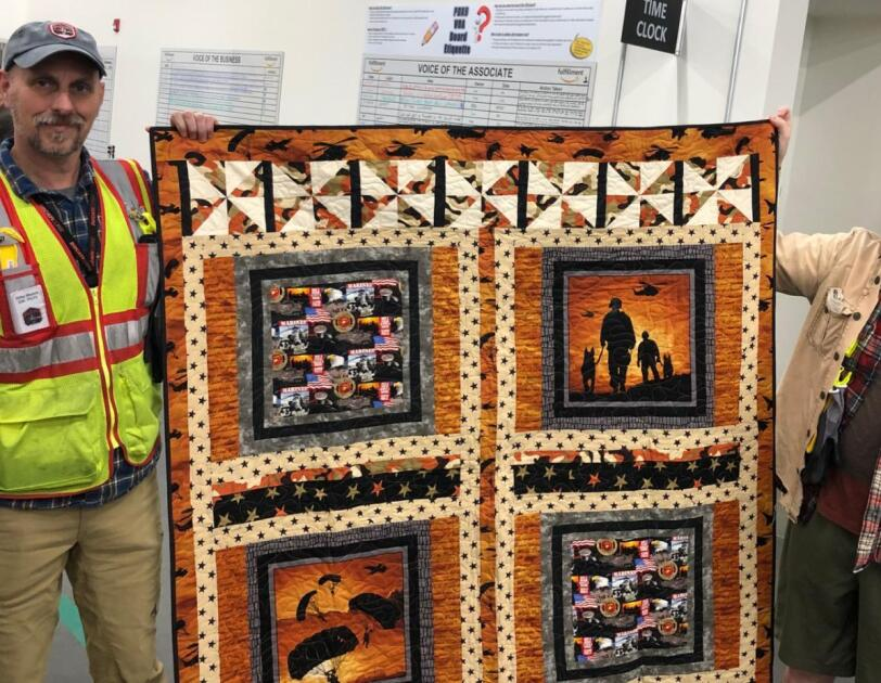 Amazon associate holds up a custom quilt with his General Manager, whom the quilt was gifted to.