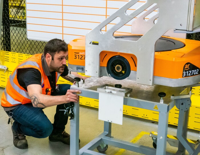 Raúl Cruz, técnico senior de mantenimiento en robótica, reparando un robot. En primer plano está Raúl, con el pelo negro y barba, vestido con una camiseta negra y el chaleco naraja. Observa atentamente un robot que está en una mesa pero alzado por una grúa, con lo que Raúl puede observar la parte inferior.