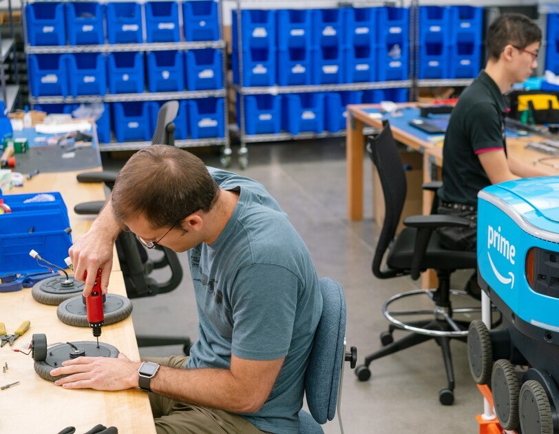 A man uses a tool as he works on a wheel for Scout. Behind him sits a Scout robot, and another man is seen working as well.