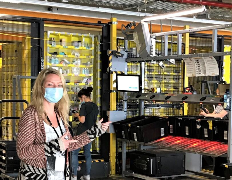 Eine blonde Frau mit Mundschutz in einer Lagerhalle