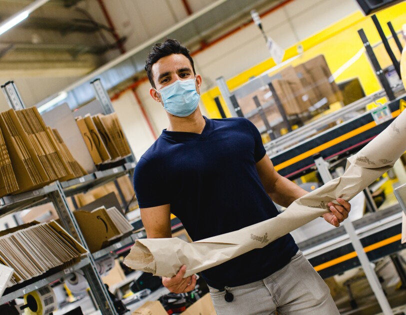 Ein Mitarbeiter mit Mundschutz an einer Packstation