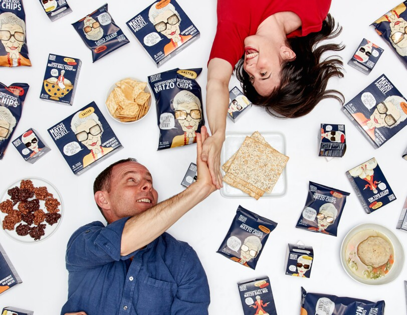 A woman lies on her back, with her right hand extended above her head as she gives a man, also lying on the ground, a high five. Around them are packages of matzo and other products.