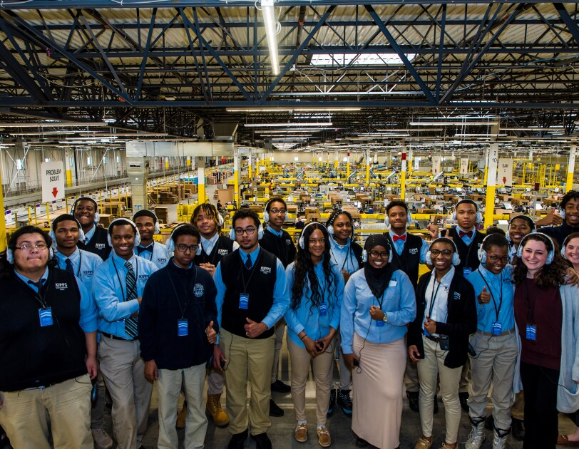 High school students wearing school uniforms pose as a group in an Amazon fulfillment center while taking a tour of the facility.