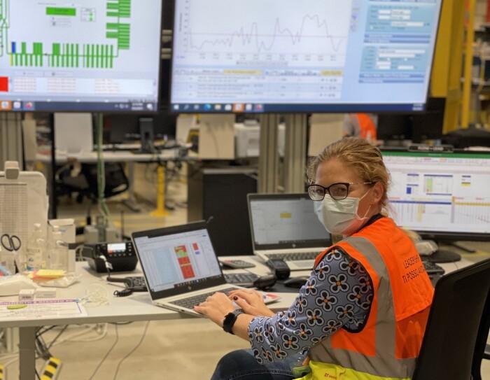 Donna seduta davanti ad un PC in un centro operativo Amazon. Indossa una mascherina chirurgica, ha i capelli biondi legati.