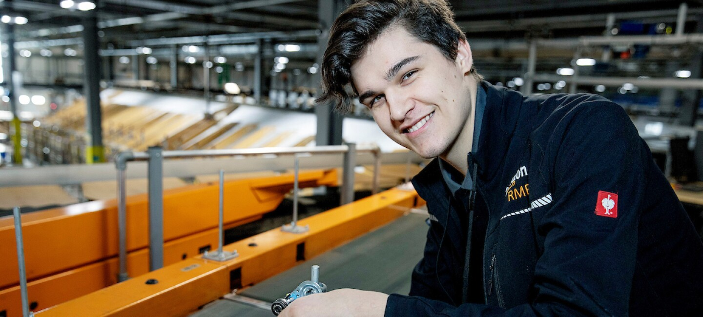 Apprentice, Danny Winn, pictured fixing a conveyor belt and smiling at the camera