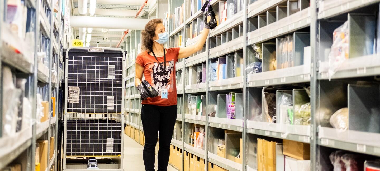 Während der Arbeit im Logistikzentrum trägt die Mitarbeiterin einen Mundschutz.