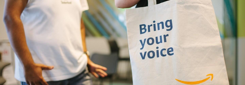 """Immagine che mostra persone all'interno di una sede Amazon con shopper in primo piano con scritta """"Bring your voice"""""""