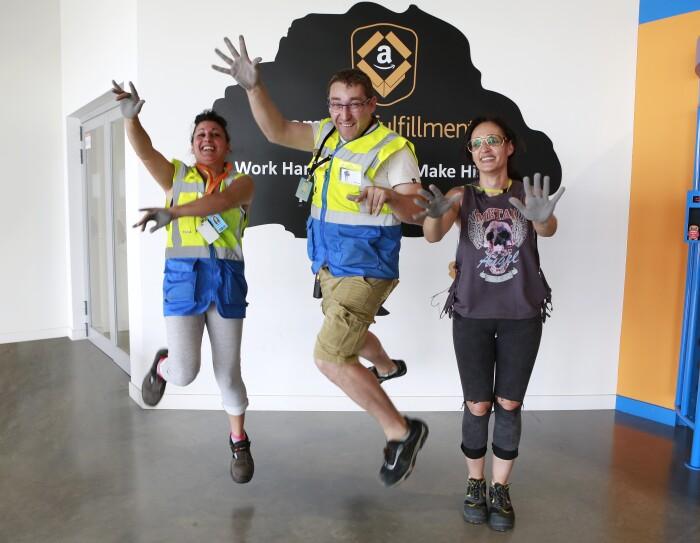 Patricia Alonso, Maribel Salcedo y Marius Dumitrescu aparecen en la entrada del centro logístico saltando y mostrando las palmas de sus manos pintadas de color gris. Están sonriendo mirando a cámara. Marius se enceuntra en medio.