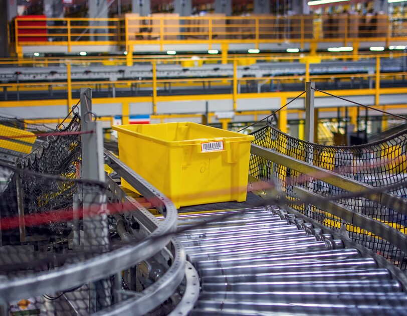 A yellow plastic container slides along metal rollers in a warehouse space.