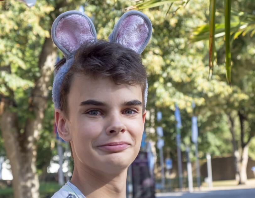 Die Poträtaufnahme zeigt einen Jungen von ca. 10 Jahren der Plüsch-Mäuseohren trägt. Er hat braune Augen, blickt direkt in die Kamera.