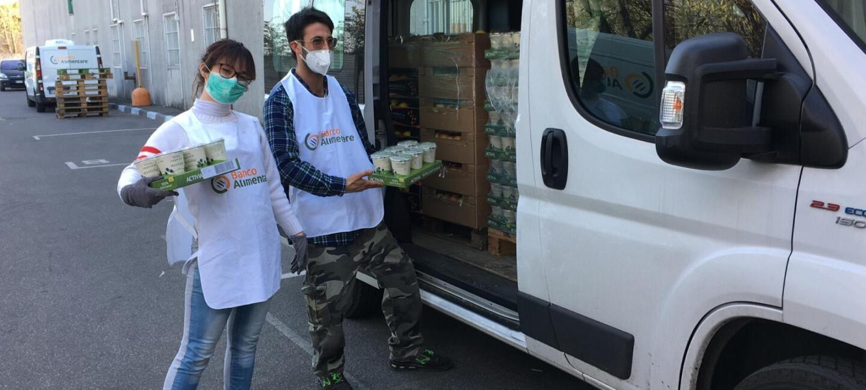 Due volontari di Banco Alimentare Lombardia davanti a un furgone con i pasti.