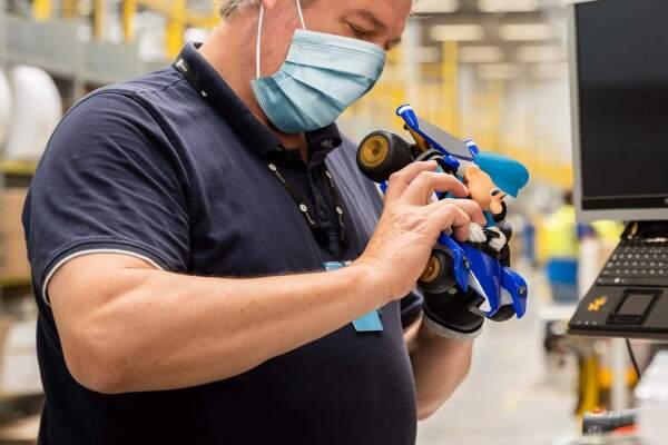Ein Mann mit dunkelblauen T-shirt schaut sich ein blaues Spielzeugauto an.