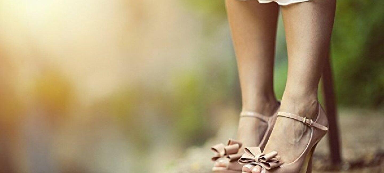 Une paire chaussures et le bas d'une robe portées par une personne qui se tient sur un rocher