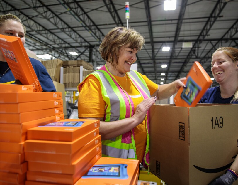 A woman on the right side of the image holds a cardboard box marked with the Amazon logo. Two other women work together to load Kindle Fire's into the cardboard box.