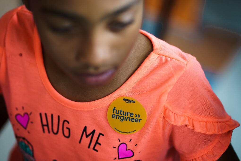 "A young girl with a ""future engineer"" sticker on her shirt."