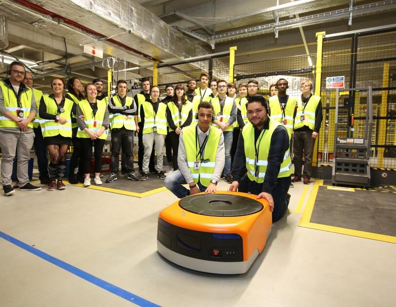 Eine Gruppe von Schülern, ausgestattet mit gelben Besucherwesten, posiert für das Gruppenfoto im Logistikzentrum. Vor ihnen: einer der Transportroboter, die in Winsen eingesetzt werden.
