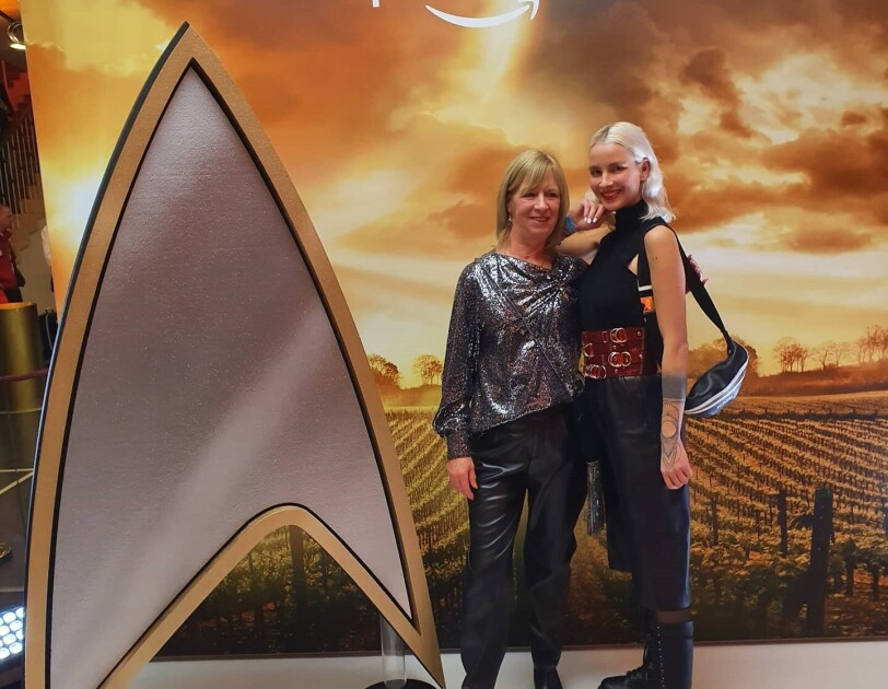2 Frauen stehen rechts vor einem großen Star Trek Logo.