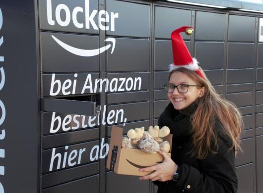 Eine Frau mit Brille und langen Haaren hält ein Amazon Karton vor einem Locker. Sie trägt eine rote Nikolausmütze. im Paket ist ein Elch zu sehen.