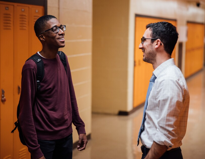 A teenage boy and a man in a necktie and button-down shirt talk in a school hallway.