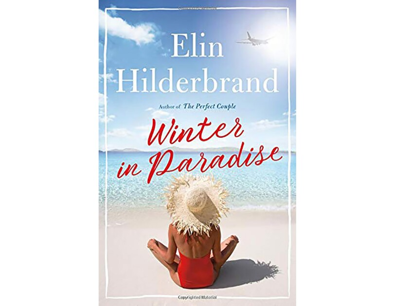 "Book cover for ""Winter in Paradise"" by Elin Hilderbrand snows a tanned woman in a red halter one-piece swim suit and straw sitting cross legged on the beach, looking out toward the ocean."