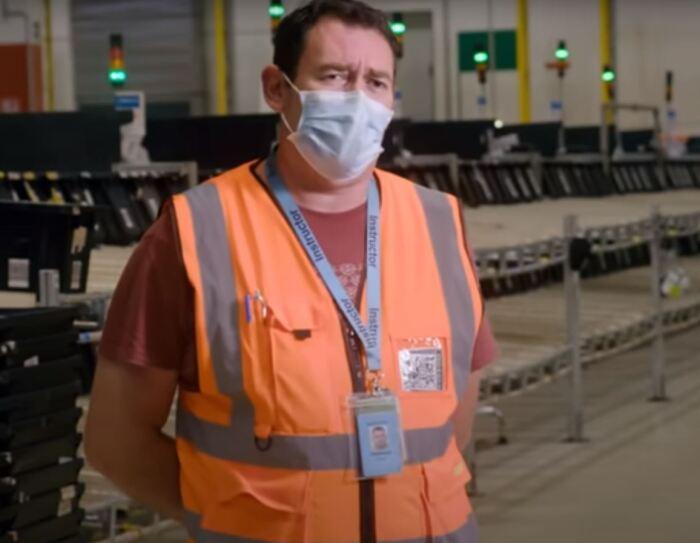 Uomo ripreso a mezzo busto all'interno di un magazzino Amazon. Indossa una mascherina chirurgica sul volto e un giubbino catarinfrangente arancione. Al collo porta appeso un cordino porta-badge blu e una t-shirt color mattone.