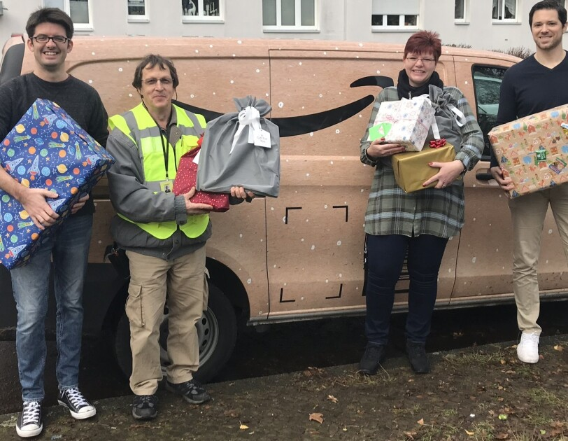 Mitarbeiter stehen vor einem Amazon Xmas Van und halten Geschenke.