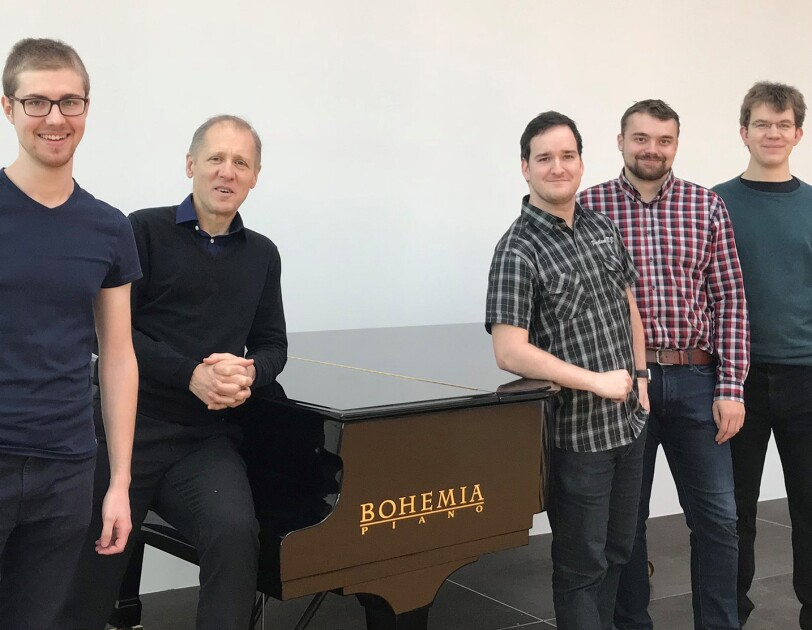 A group of four students and their advisor stand near a Bohemia piano.
