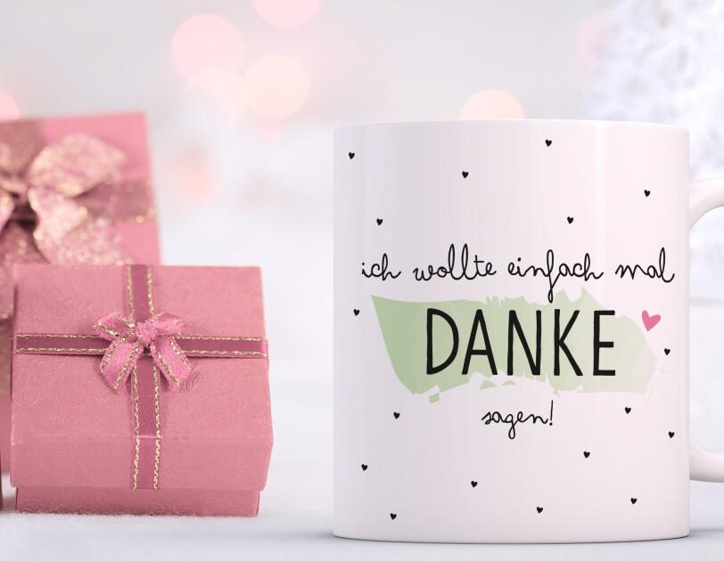 """Eine weiße Tasse mit der Aufschrift """"Ich wollte einfach mal Danke sagen"""" steht vor einem weißen Hintergrund mit rosafarben eingepackten Geschenken."""