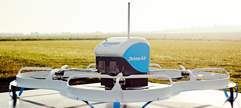 Biało-niebieski dron z logiem Prime Air oraz Amazon, umiejscowiony na metalowej powierzchni, w tle szerokie pole