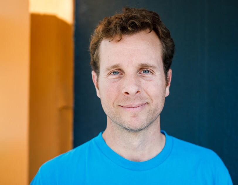 Jamie Siminoff, Gründer des Unternehmens Ring. Er trägt ein hellblaues T-Shirt und blickt direkt in die Kamera.