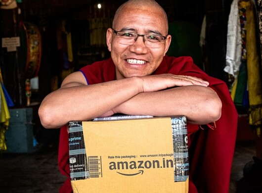 Monk smiling with Amazon box