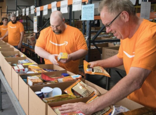 Amazon employees wearing orange shirts pack boxes of supplies to help in the company's disaster relief efforts