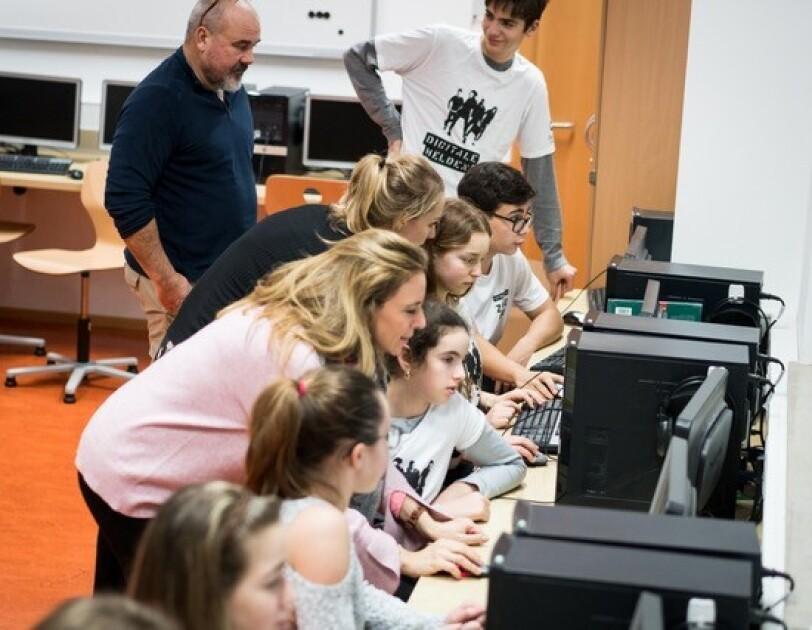Mädchen und Jungen sitzen vor Computer-Bildschirmen. Sie schauen alle in die Bildschirme.
