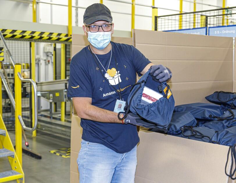 Amazon Helfer vor einem großen Karton mit Rucksäcken.