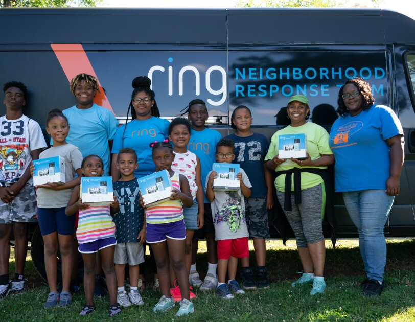 Children in Newark, New Jersey with blue t-shirts that have Ring on them. They are standing in front of van that is a Ring neighborhood response van.
