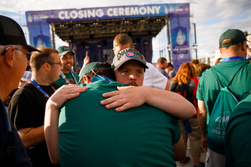 A man embraces another male, while celebrating the USA Games closing ceremony. In the background, more event attendees appear to celebrate, with a stage setup in the distance.