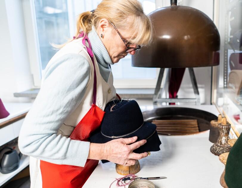 Eine Frau steht an einem weißen Tisch und hat einen dunkelblauen Hut in den Händen. Sie hat blonde Haare und träge eine Brille.