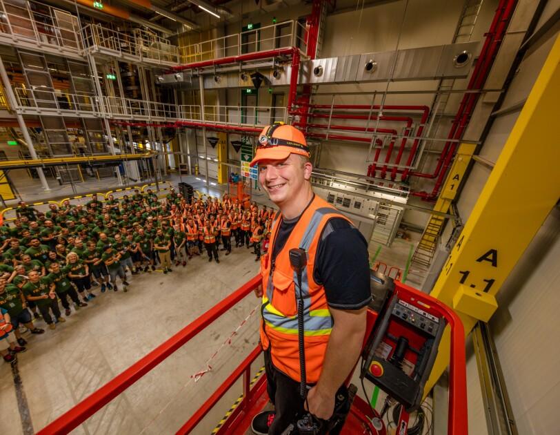 Ein Ingenieur blickt von oben auf die Halle und auf die ca. 300 Mitarbeiter, die sich dort versammelt haben.