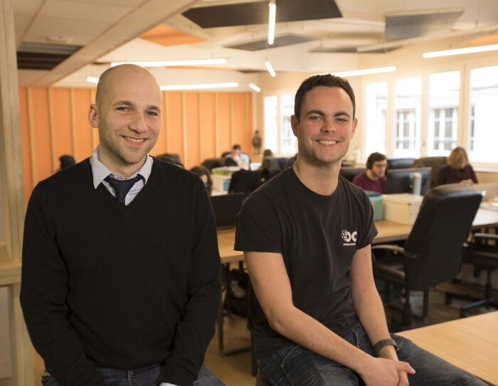 Les fondateurs d'OpenClassrooms sont assis dans l'open space de leur bureau. A l'arrière-plan des employés travaillent sur leur ordinateur