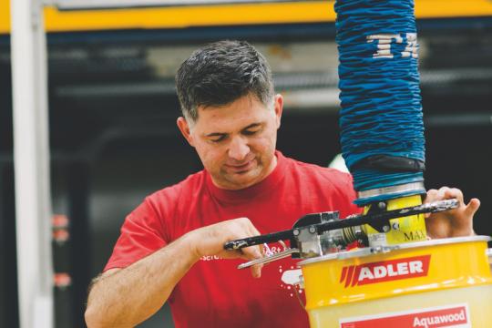Ein dunkelhaariger Mann mit rotem T-shirt steht vor einer Maschine und hat einen gelben Farbeimer in den Händen. Er lächelt und schaut auf den Farbeimer.