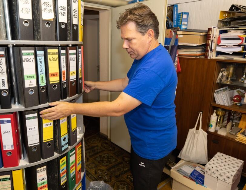 Ein man im blauen Tshirt steht vor einem Aktenschrank und sucht nach einem Ordner.