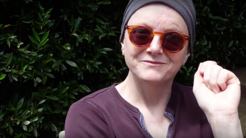 A woman wearing a head scarf, sunglasses, and a tee shirt shares a small smile with the photographer.