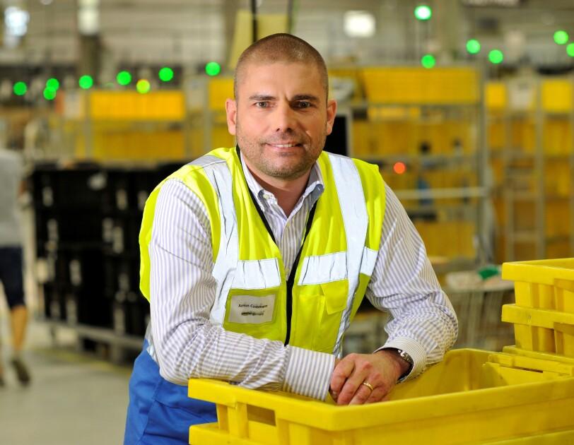 Ein Mann in gelber Sicherheitsweste lehnt sich lässig auf einem Stapler gelber Transportbehälter im Logistikzentrum