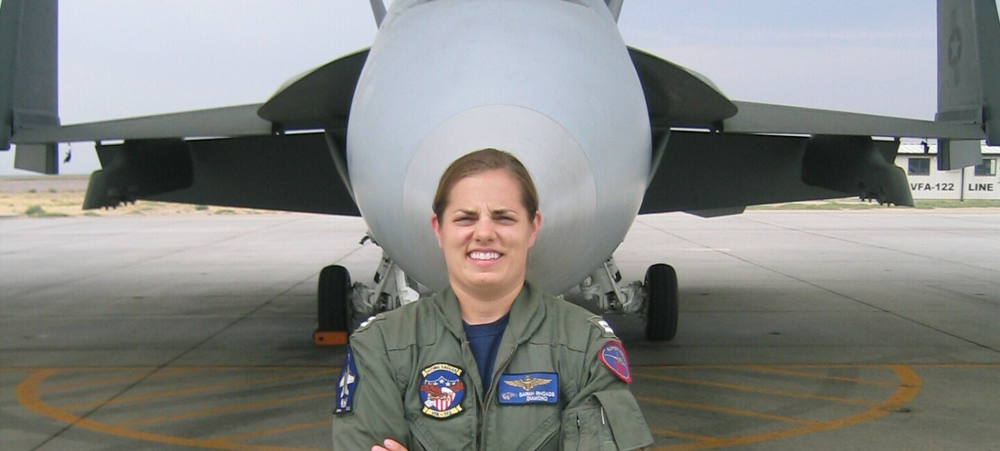 A woman in a United States Navy flight suit stands in front of a fighter jet with her arms crossed.