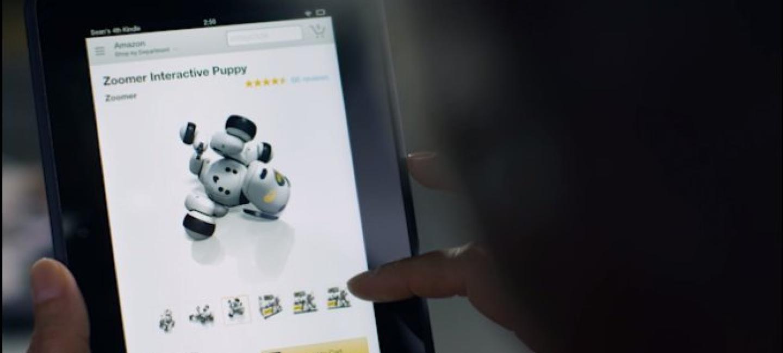 Schermo di un device aperto su una pagina prodotto di Amazon. Il device è tenuto in mano da un uomo di cui si vedono solo le dita. La pagina prodotto mostra un pupazzo interattivo.