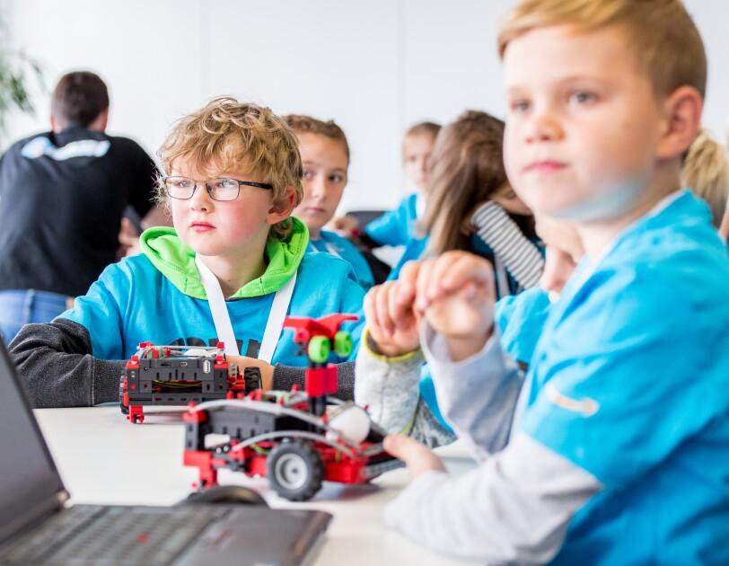 Auf einem Tisch steht ein Laptop, vor dem ein Junge im blauen T-Shirt sitzt. Im Hintergrund ist ein weiterer Junge zu sehen. Beide haben vor sich einen Fischertechnik-Transportroboter.