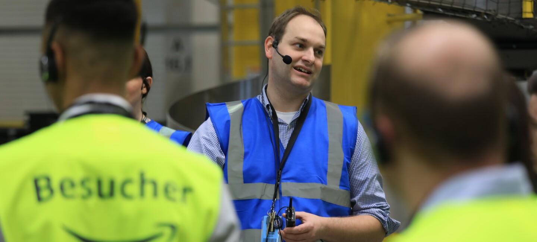 Ein Tourguide in blauer Sicherheitsweste steht vor Besuchern, die eine gelbe Sicherheitsweste tragen.