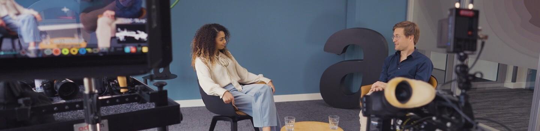 Cherifa und Ole sitzen im Amazon Büro und unterhalten sich.